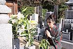 Japan, Kyoto, woman in kimono praying in cemetery