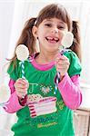 A girl holding two egg-shaped cake pops