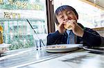 Boy eating Hamburger in restaurant