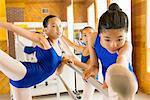 Ballerinas warming up at the barre in ballet school