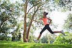 Young woman jogging through park