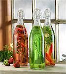 Three bottles of pickled herbs on windowsill