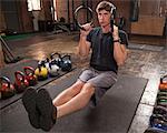 Bodybuilder on gym floor using rings