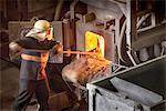 Steel worker poking furnace in steel foundry