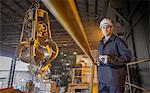 Portrait of steel worker overseeing mechanical grabber in steel foundry