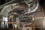 Steel worker overseeing industrial magnet at work in steel foundry