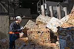 Steel worker examining scrap metal bales outside foundry