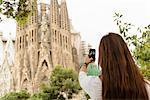 Young female tourist photographing Sagrada Familia, Barcelona, Spain