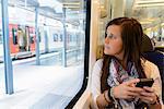 Young female tourist on local train, Catalonia, Spain