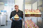 Chocolatier holding a giant chocolate cupcake