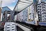 Forklift lifting aluminum ingots onto truck