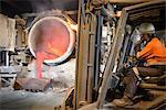 Worker monitoring molten aluminum running into mold