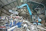 Workers and excavator lifting scrap metal in warehouse