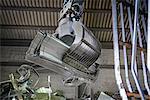 Excavator lifting scrap metal in warehouse