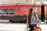 Female backpacker arriving in train station, Salzburg, Austria