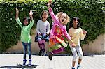 Four girls jumping in garden