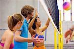 Friends enjoying indoor beach volleyball