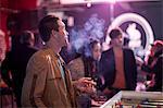 Man smoking cigarette in bar