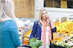 Young women buying produce in indoor market