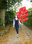 teen girl running with a lot of heart ballons