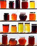 Assorted jars of jam on wooden shelves