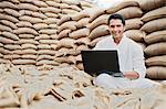 Man using a laptop in a grains market, Anaj Mandi, Sohna, Gurgaon, Haryana, India