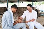 Man showing sample of wheat to a customer, Anaj Mandi, Sohna, Gurgaon, Haryana, India