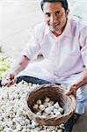 Man picking garlic bulbs from a market stall, Sohna, Gurgaon, Haryana, India