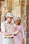 Mature couple looking photos on a digital camera, Lodi Gardens, New Delhi, India