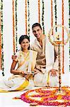 South Indian couple near a rangoli of flowers at Onam