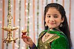Girl burning oil lamps on Diwali