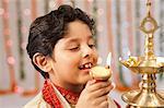 Boy burning oil lamps on Diwali