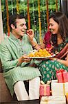 Woman feeding gulab jamun to her husband on Diwali