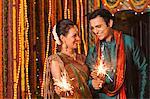 Couple burning fire crackers on Diwali