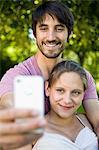 Happy couple taking self portrait outdoors