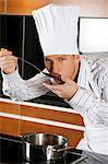 Cook in kitchen tasting food