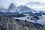 A snowy view of Sassolungo and Sassopiato Mountains behind the Alpe di Siusi ski area in the Dolomites, South Tyrol, Italy, Europe