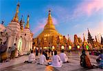Shwedagon Paya (Pagoda) at dusk with Buddhist worshippers praying, Yangon (Rangoon), Myanmar (Burma), Asia