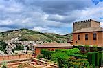 Patio de Machuca in Nasrid Palaces in La Alhambra and Sacromonte in the background in Granada, Spain