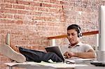 Young man using digital tablet wearing headphones, feet up