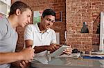 Young men using digital tablet