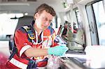 Paramedic in ambulance checking equipment list