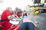 Three paramedics tending patient on road