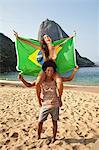 Couple on beach with Brazilian flag, Rio de Janeiro, Brazil