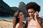 Couple on beach, man on cell phone, Rio de Janeiro, Brazil