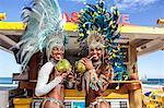 Two samba dancers drinking coconut drinks, Ipanema Beach, Rio, Brazil