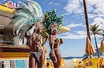 Samba dancers in costume with coconut drinks, Ipanema Beach, Rio De Janeiro, Brazil