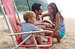 Family on beach, boy sitting on chair