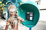 Samba dancer using pay phone, Ipanema Beach, Rio De Janeiro, Brazil
