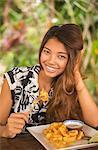 Young Asian woman eating deep fried prawns.